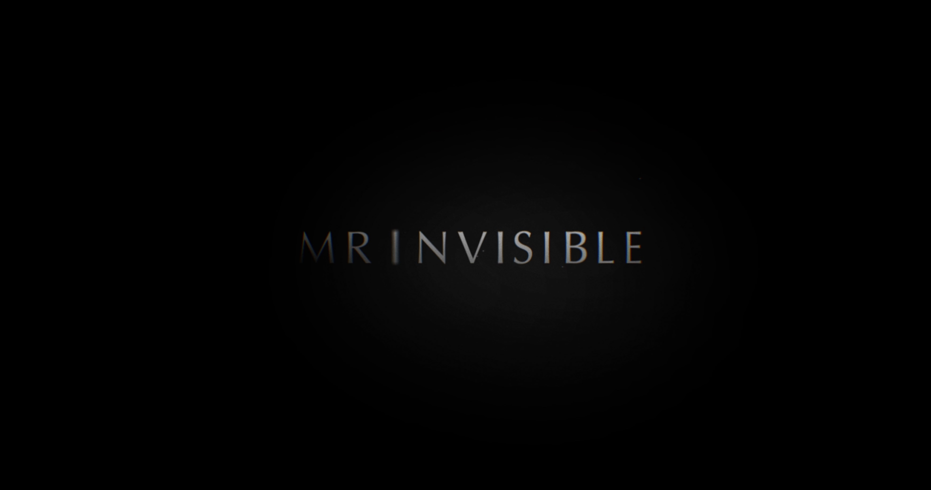 Black screen with the letters 'invisible' in heavy shadow