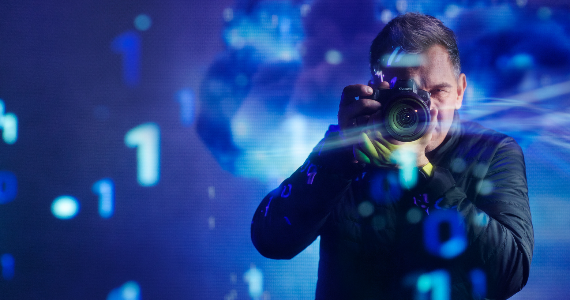 A man holds a Canon EOS R camera in hand, data is projected over him