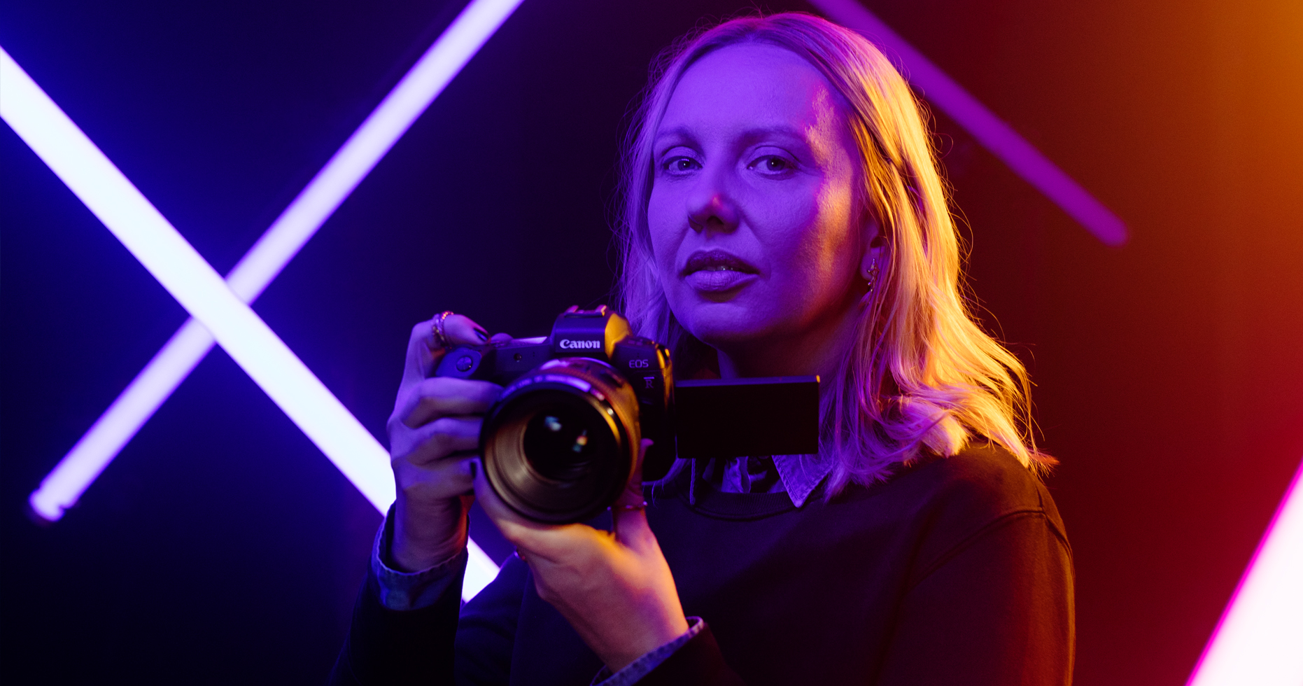 Maria Eriksson holds her Canon EOS R Camera in hand. She is in a studio lit with neon lights.
